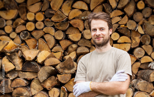 Happy man in front of stacked chopped firewood