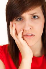 Die junge Frau hat Zahnschmerzen und hält sich die Wange