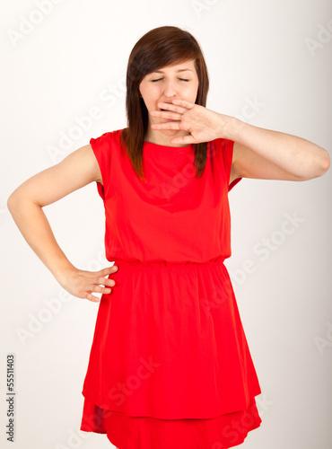 Die junge Frau steht müde vor der Kamera