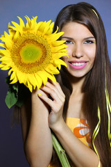 Portrait of a beautiful smiling girl with a sunflower