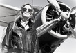 Young beautiful woman pilot in front of  airplane.