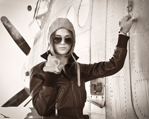 Young beautiful woman pilot on a airplane.