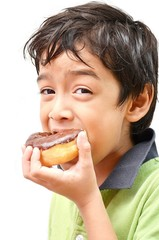 Little boy eating donut chocolate white background