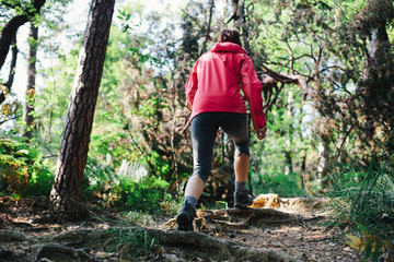 Woman hiking in the woods going uphill