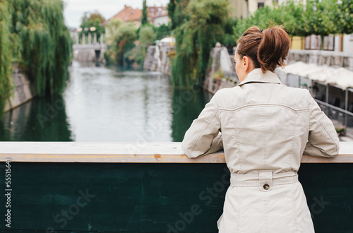Woman standing on bridge looking down at river