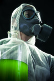 Man with gas mask carrying hazardous chemical waste