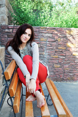 Dark-haired girl sitting on the bench