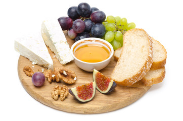 cheese, bread, figs, grapes, honey and nuts isolated