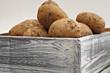 neue Kartoffeln ungewaschen in Holzkiste