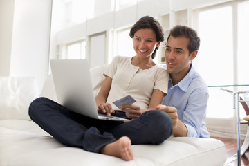 Couple using credit card to shop online, laptop at home