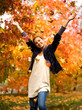 teen girl throwing leaves in autumn