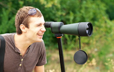 Positive man who is watching in spotting scope.
