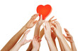 Many hands reaching for red heart