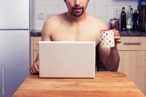 Naked man at home with laptop and coffee - 55528610