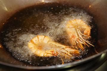 Prawns being fried in wok pan