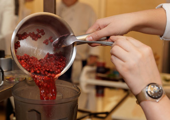 Chef is cooking berry sauce in blender