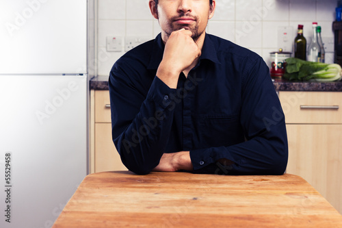 Man at kitchen table thinking