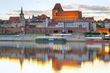 Torun old town at sunset reflected in the river, Poland