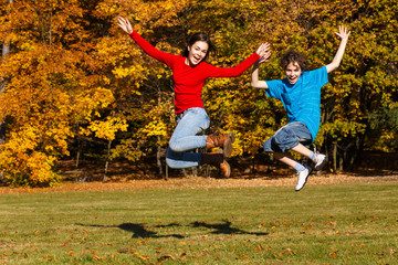 Girl and boy running, jumping in park
