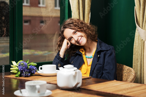 Happy young woman drinking tea at restaurant