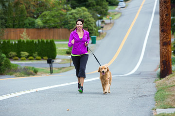 woman running with golden retriever