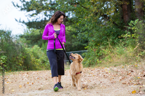 woman walking with dog - 55535093