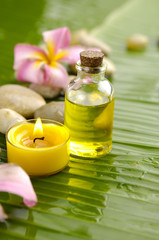 Massage oil with candle and Plumeria and stone on banana leaf