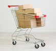 Shopping cart with carton, on gray background