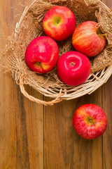 Fresh red apples in basket over wooden background
