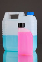 Blue and pink liquids for car in canisters on grey background