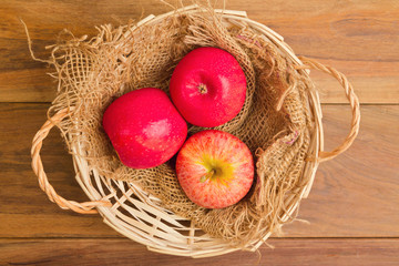 Apples in basket on wooden table