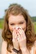 Junge Frau beim Nase putzen