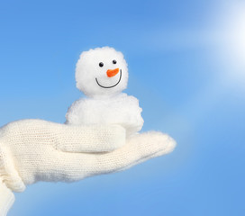 Hands in white gloves holding snowman against blue sky.