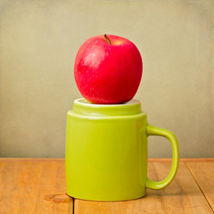 Red apple on top of green cup. Healthy eating concept