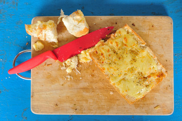 Top view garlic bread with red knife on the chopping block