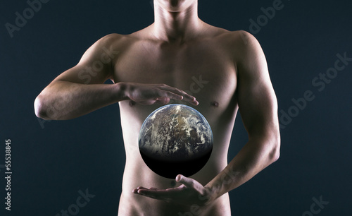 Young Muscular Man with a Globe on black background