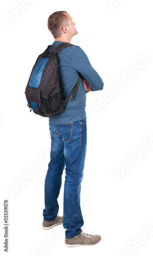 Back view of man with photographic backpack looking up