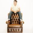 Mann sitzt auf Sessel