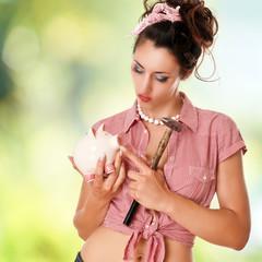 Mädchen mit Sparschwein hält einen Hammer