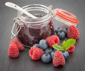 Raspberry and bilberry jam in a jar and fresh berries