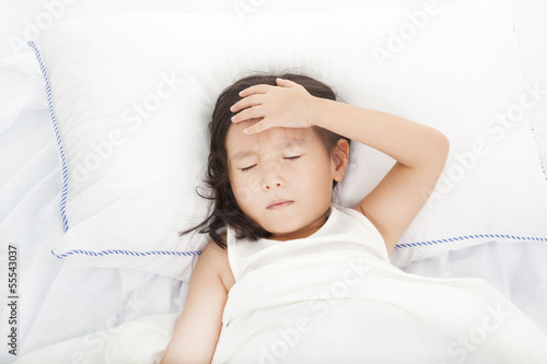 Little girl with illness on the  bed