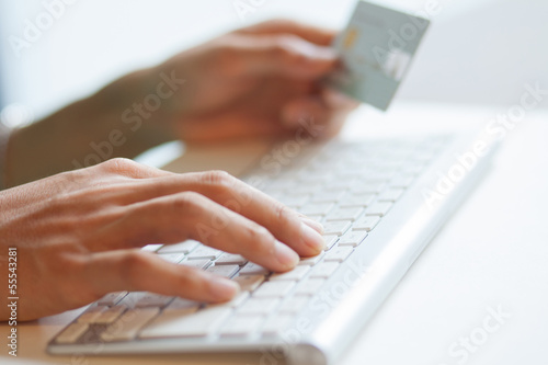 Holding credit card and typing security codes on keyboard