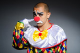 Sad clown against dark background