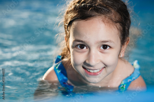Girl swims in the pool