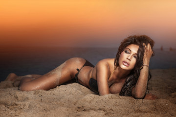 Sensual brunette beauty posing on the beach.