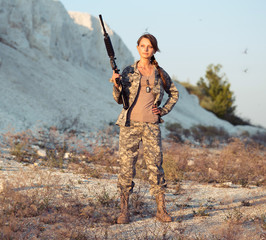 Young female soldier dressed in a camouflage with a gun in the l