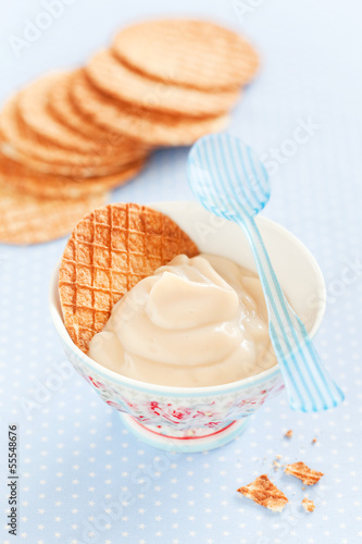 Caramel cream in a ceramic bowl and waffles, selective focus