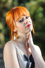 Red haired cute young girl touching her neck at outdoor