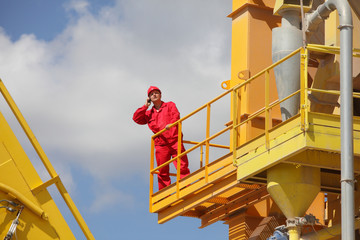 worker in red uniform  calling on phone on industrial platform