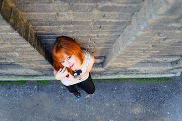 Red haired cute young girl standing beside the wall top shot